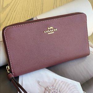 Coach wine-color wristlet phone case wallet.